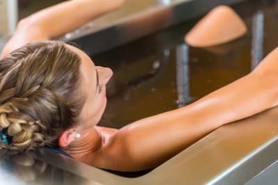 Senior woman enjoying mud bath alternative therapy