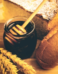 Healthy jar of honey with bakery products on wooden background.
